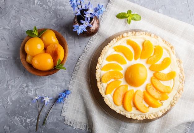 桃のチーズケーキと灰色のコンクリート背景に青い花を持つセラミック花瓶。上面図。