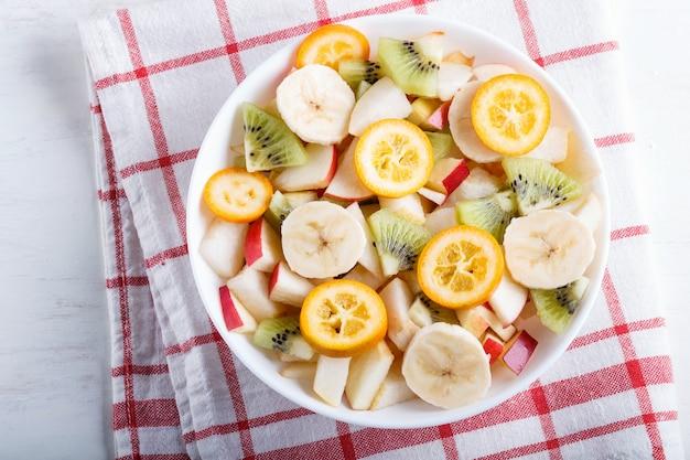 バナナ、リンゴ、ナシ、キンカン、キウイのリネンのテーブルクロスの上のベジタリアンサラダ