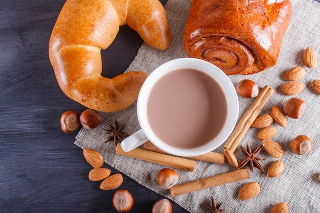 Чашка горячего шоколада с орехами, булочками и специями на черном деревянном
