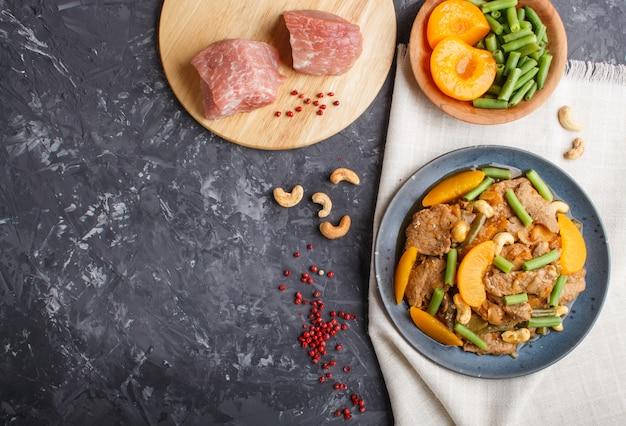 揚げ豚肉、モモ、カシューナッツ、インゲン、黒いコンクリートの背景