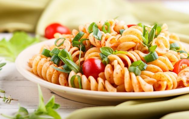 Паста фузилли с томатным соусом, помидорами черри, листьями салата и зеленью