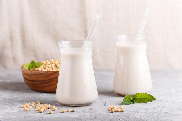 灰色のコンクリートの大豆とガラスと木の板の有機非乳製品豆乳。