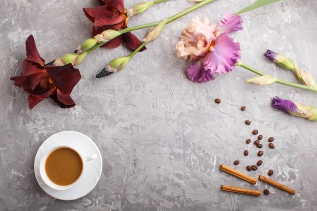 Фиолетовые и бордовые цветы ириса и чашка кофе на сером бетоне