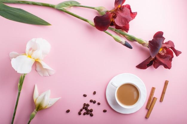 Белые и бордовые цветы ириса и чашка кофе на пастельно-розовом
