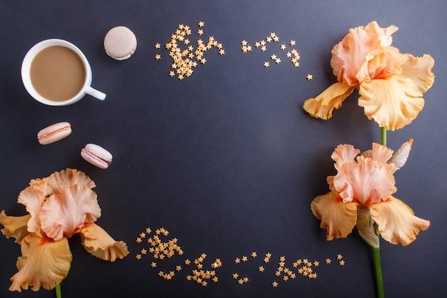 Цветы оранжевого ириса и чашка кофе на черном