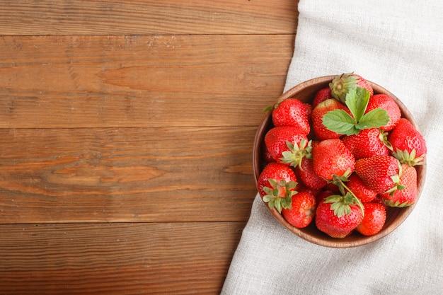 木製のボウルに新鮮な赤いイチゴ。上面図。