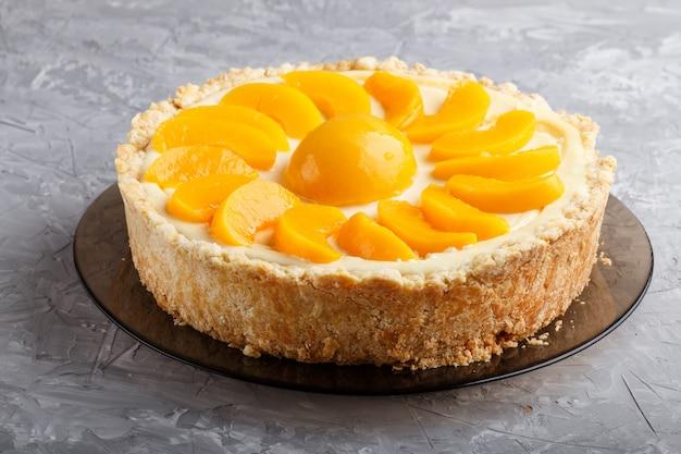 灰色のコンクリートの桃のチーズケーキ。側面図。