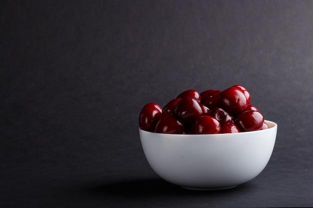 Свежая красная черешня в миску. вид сбоку.