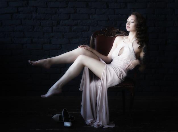 ピンクのドレスの若い美しい茶色の髪の女性の肖像画。