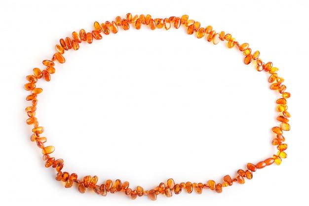 Оранжевые янтарные бусы, изолированные на белой поверхности