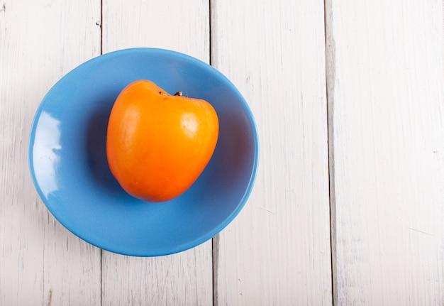 Спелая оранжевая хурма в синюю тарелку на белом фоне деревянные