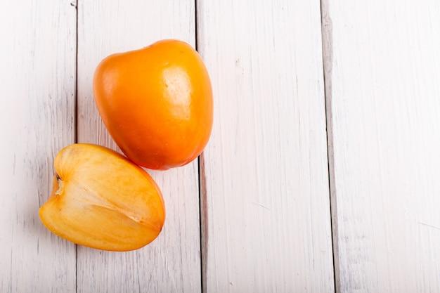 Спелая оранжевая хурма на белом фоне деревянные
