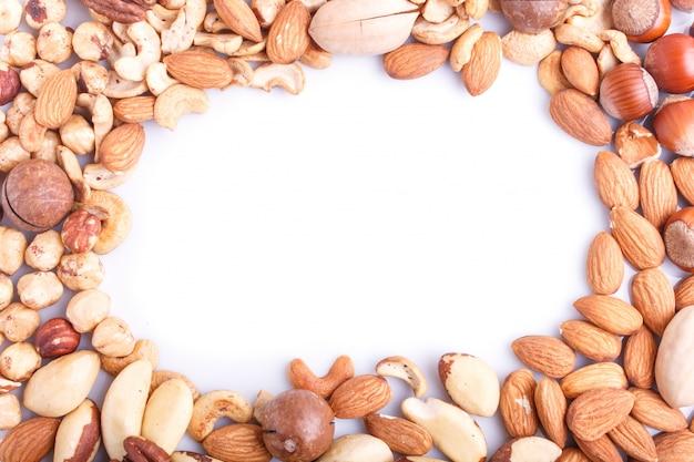 白い背景にさまざまな種類のナッツから作られたフレーム。