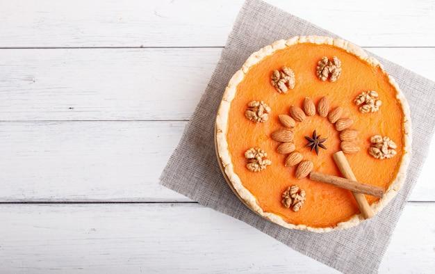 白い木製の表面上のナッツで飾られた伝統的なアメリカの甘いパンプキンパイ。