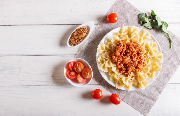 白い木製のミンチ肉とファルファッレボロネーゼパスタ。