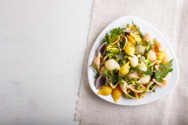 リネンテーブルクロスに新鮮な青果のコンキリエ色パスタ