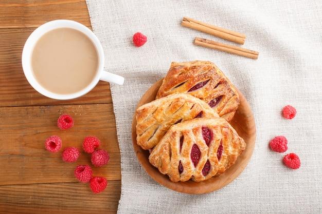 リネン繊維とコーヒーカップと木製の背景にいちごジャムとパイ生地パン