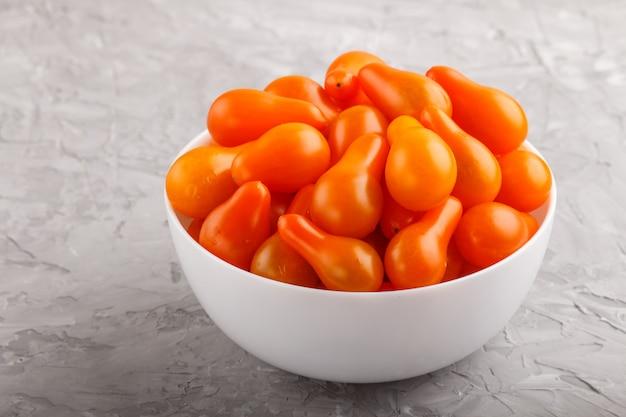 灰色のコンクリート背景に白いセラミックボウルで新鮮なオレンジグレープトマト