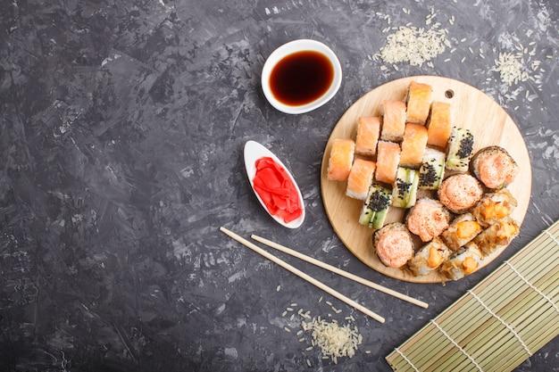 Смешанные японские маки суши роллы с палочками, имбирь, соевый соус, рис на черном фоне бетона, вид сверху.