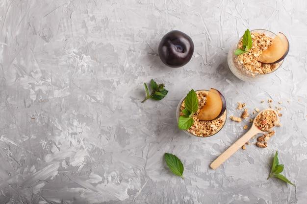 Йогурт со сливой, семена чиа и мюсли в стеклянной и деревянной ложкой. фон вид сверху