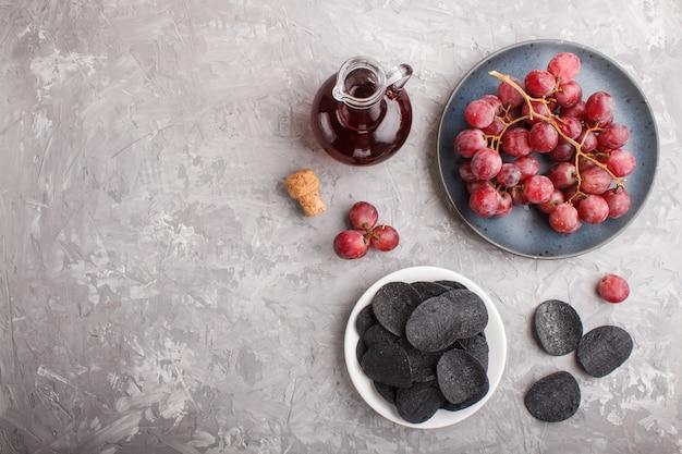 黒いポテトチップスと炭、ガラスのバルサミコ酢、青いセラミックプレートの赤いブドウ。上面図。