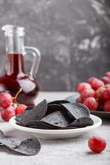 黒ポテトチップス、炭、ガラスのバルサミコ酢、青いセラミックプレートの赤ブドウ