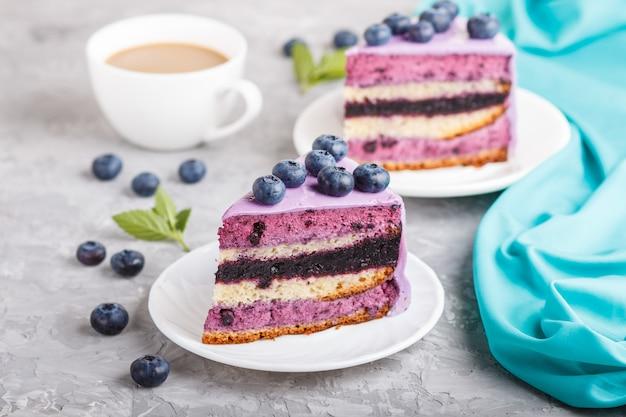Домашний торт с суфле кремом и черничным джемом с чашкой кофе. вид сбоку.