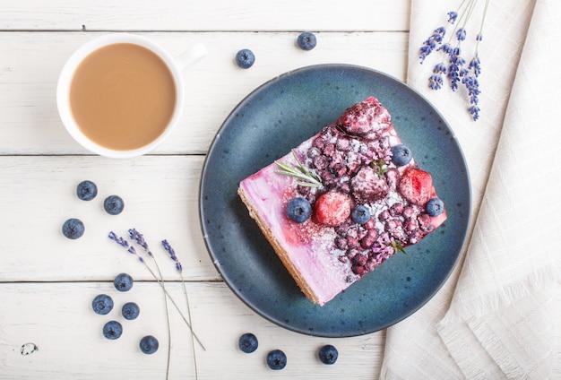 一杯のコーヒーと新鮮なブルーベリーと青いセラミックプレートにミルククリームとブルーベリージャムのベリーケーキ。上面図。