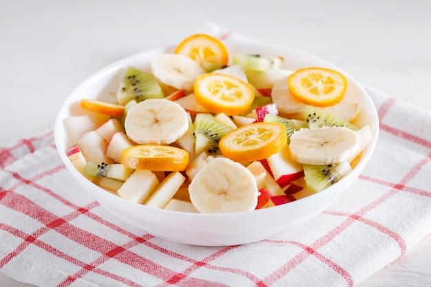 リネンのテーブルクロスにバナナ、リンゴ、梨、キンカン、キウイのベジタリアンサラダ