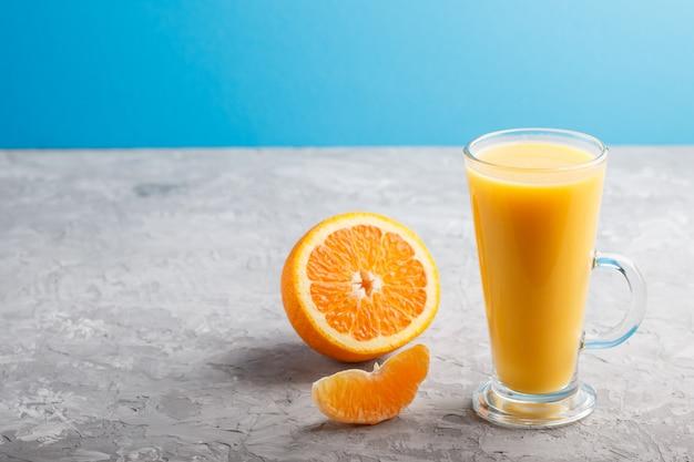 灰色と青の背景にオレンジジュースのガラス。側面図
