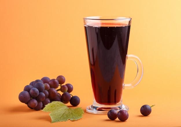 オレンジ色の背景に赤いグレープジュースのガラス。側面図
