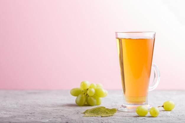 グレーとピンクの背景に緑のグレープジュースのガラス。側面図、コピースペース。