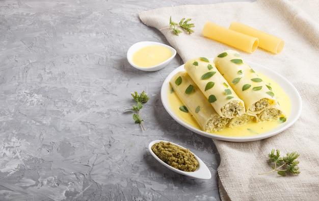 Паста каннеллони с яичным соусом, сливочным сыром и листьями орегано на сером бетоне