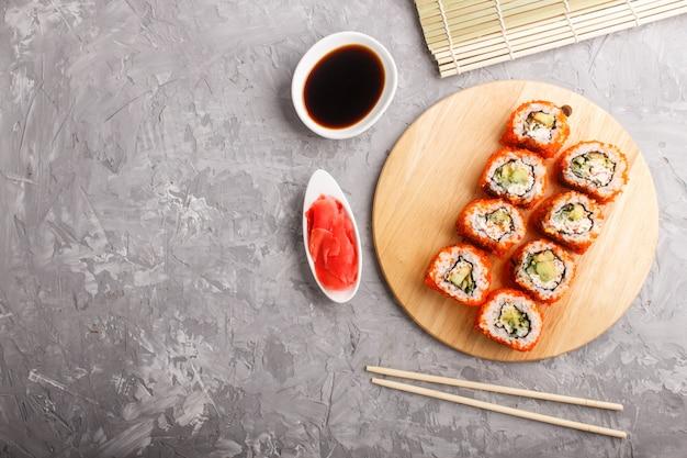 Японские маки суши роллы с икрой летучей рыбы на деревянной доске на серый бетон