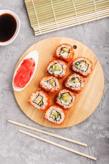 日本の巻き寿司は灰色のコンクリート背景に木の板にトビウオを巻きます。トップビュー、クローズアップ。