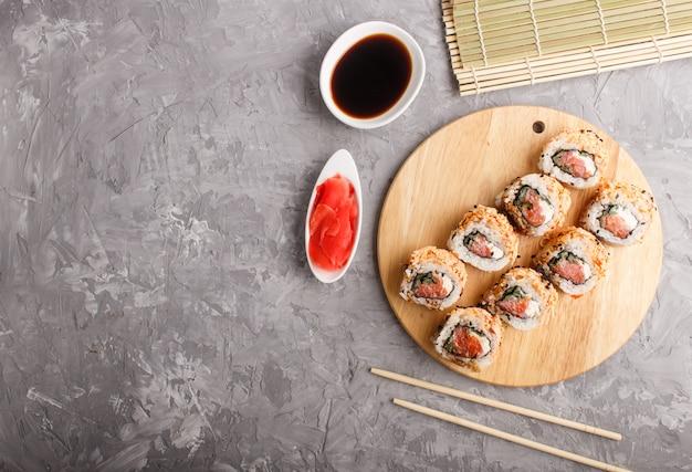 日本の巻き寿司、サーモン、ゴマ、灰色のコンクリートの木製ボード上