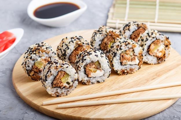 Японские маки суши роллы с лососем, кунжутом, огурцом на деревянной доске на сером бетоне