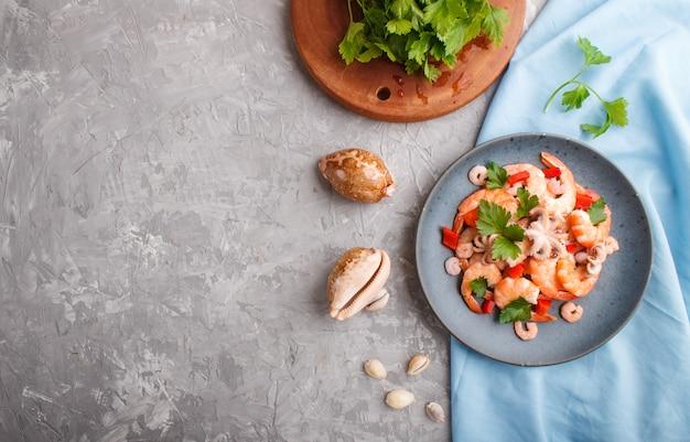 Вареные креветки или креветки и маленькие осьминоги с зеленью на синей керамической тарелке на сером бетонном фоне