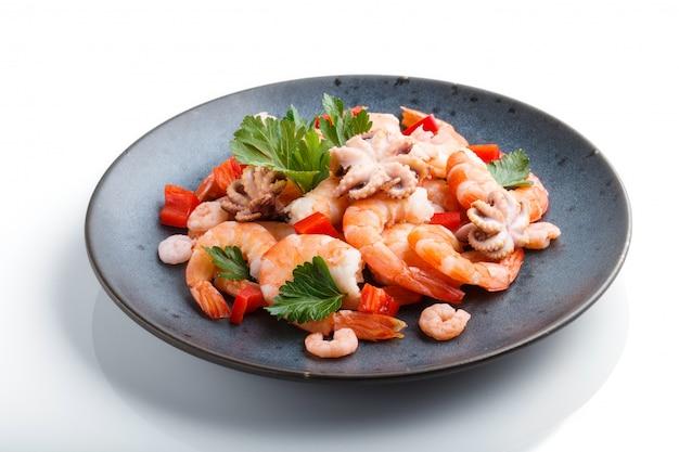 Вареные креветки или креветки и маленькие осьминоги с зеленью на синей керамической тарелке на белом фоне