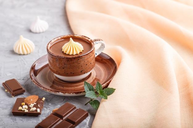Чашка горячего шоколада и кусочки молочного шоколада с миндалем