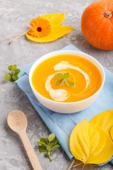 Традиционный суп из тыквы крем в белый шар на сером фоне конкретных с голубой салфеткой.