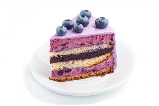 Домашний торт с суфле кремом и черничным вареньем, изолированные на белом фоне.