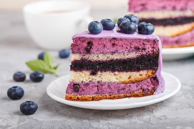 Домашний торт с суфле-кремом и черничным джемом с чашкой кофе на сером бетонном фоне