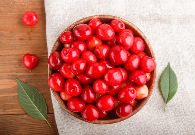木製のボウルに新鮮な赤い甘いチェリー。上面図。