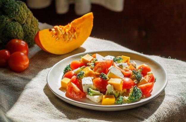 Вегетарианский салат на белой керамической тарелке