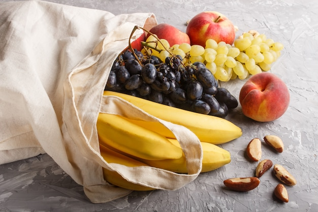 Плоды в хлопчатобумажной текстильной белой сумке на сером бетонном фоне. нулевая концепция покупки, хранения и переработки отходов. вид сбоку, крупным планом