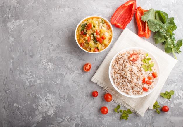 灰色のコンクリート背景に白いボウルに野菜とオレガノの煮込み玄米