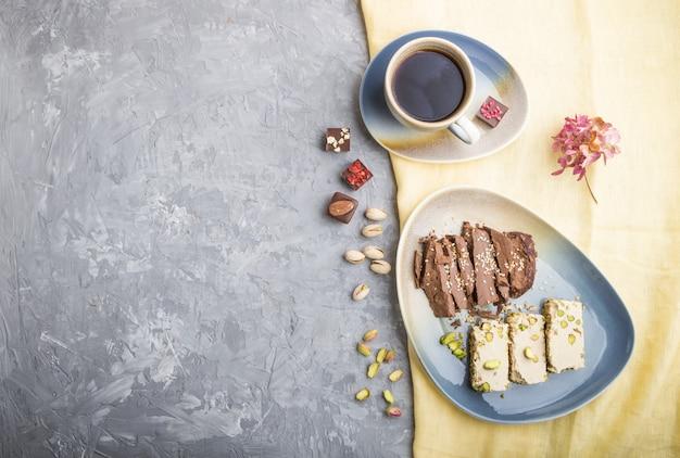 Традиционные арабские сладости с кунжутной халвой с шоколадом и фисташками и чашкой кофе на сером бетоне