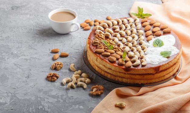 キャラメルクリームと灰色のコンクリート背景にコーヒーのカップとナッツの自家製ケーキ
