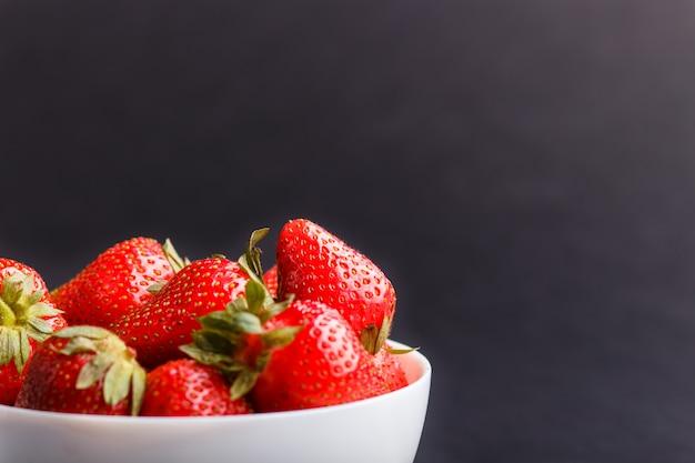 黒い背景に白いボウルで新鮮な赤いイチゴ